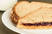 Peanut butter and jelly sandwich on wheat bread with glass of milk in background
