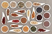 Large nut and seed food selection in porcelain bowls over hessian background.
