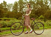 Young woman in dress posing with retro bicycle in the park. Vintage style.