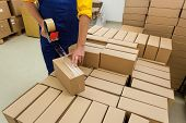 stock photo of dispenser  - Warehouse worker packaging product for a customer - JPG