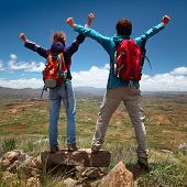 Hikers with backpacks standing on top of a mountain with raised hands