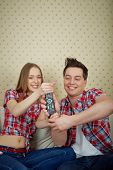 Portrait of young couple fighting for remote control in front of TV set