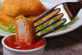 picture of impaler  - Chicken Nuggets impaled on a fork in ketchup closeup - JPG