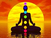 foto of kundalini  - Silhouette of a woman meditating with seven colorful chakras upon ocean by red sunset - JPG