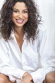 Studio portrait of a beautiful happy young woman smiling wearing an oversized men's white shirt