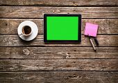 stock photo of hot coffee  - Digital tablet computer with sticky note paper and cup of coffee on old wooden desk - JPG