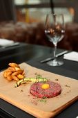 Beef tartare with french fries and avocado on restaurant table