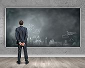 Rear view of businessman looking at chalkboard