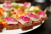 Herring canapes with onion  in plate, close-up, shallow focus