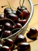 Dark Cherries In Mesh Sieve On Wooden Table