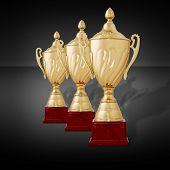 image of plinth  - Receding row of three gold trophies to be awarded as prizes to the winner with lids and plinths standing on a dark grey background - JPG