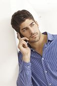 Handsome young man talking on mobile phone, looking away, leaning against wall.