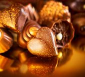 Valentine Chocolates. Assorted Chocolate Candies. Chocolate Sweets. Candy Border Design over Golden