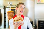 Doner kebab - friendly vendor in a Turkish fast food eatery, with a freshly made pita bread or kebab