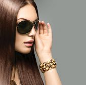 Beauty Fashion model girl with long brown hair wearing stylish sunglasses. Sexy woman portrait