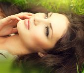 Beauty woman lying on the field and dreaming. Beautiful Girl lying on the meadow. Enjoying nature. Green Grass
