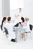 Doctors Answering Colleague In Meeting