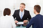 picture of counseling  - Rear view of young couple consulting financial advisor at office desk - JPG