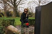 picture of grieving  - Young female grieving at cemetery - JPG