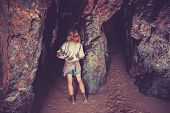 picture of cave woman  - A young woman is standing inside a rock cave - JPG