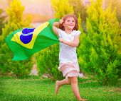 Happy little football fan, cute little girl running on the park with national Brazil flag waving on