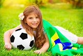 Young cheerful football fan lying down on fresh green grass with ball and big Brazil flag, happy supporter of Brazilian football team