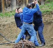 Group of determined hard co-workers pulling rope
