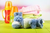 Composition with crocheted booties for baby,clothes, bottles on wooden background