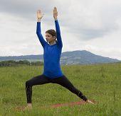 stock photo of virabhadrasana  - Man is doing Warrior Pose in yoga outdoors - JPG