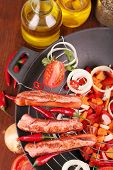 Delicious sausages with vegetables in wok on wooden table close-up