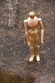 Wooden pose puppet under rain, outdoors