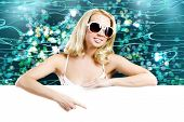 Young pretty woman in sunglasses with blank white banner