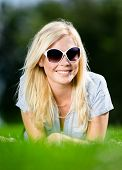 Young girl in sunglasses is lying on the grass