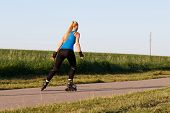 Woman Rollerblading In Summer Evening