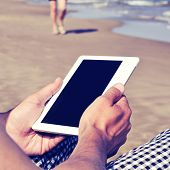 man using a tablet or an e-book on the beach, with a retro filter effect