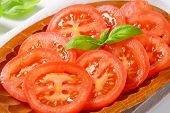 detail of  tomato slices and fresh basil on oval plate