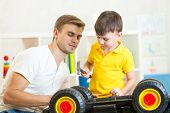 kid boy and his dad repair toy car