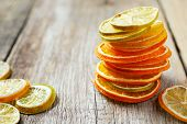 Stack Of Dried Orange And Lemon Slices On Wooden Table.