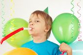 Little boy in festive hat with whistle and holiday balloons and streamer