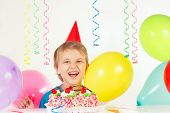 Little blonde boy in holiday hat with birthday cake and balloons