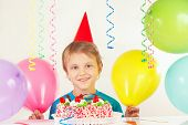 Little blonde boy in festive cap with birthday cake and balloons