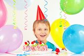 Young blonde boy in festive hat with birthday cake and balloons