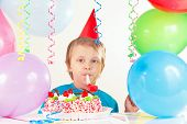 Little cute boy in holiday hat with birthday cake with whistle and festive balloons