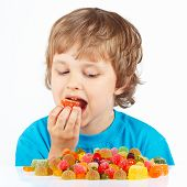 Little boy eating jelly candies on white background