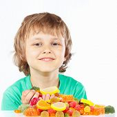 Little child with sweets and candies on white background
