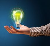 Businessman holding glowing lightbulb in his hand