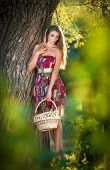 Attractive young woman in a summer fashion shot. Beautiful fashionable young girl with straw basket