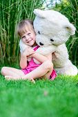 Little Cute Girl Sittinging In The Grass With Large Teddy Bear