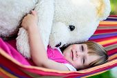 Little Cute Girl Lying On Hammock With Large Teddy Bear