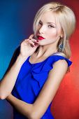 elegant beautiful women blonde with red lips in a blue dress in the Studio